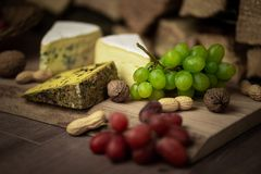 Cheese, wine and grapes - a tasty dinner royalty free stock photography