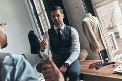 Long working day. Two young fashionable men having a discussion while spending time in the workshop stock images