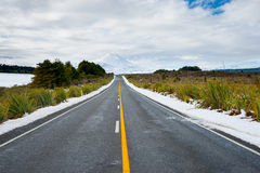 Long yellow center line along road through winter landscape lead Stock Photography
