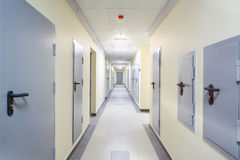 Long yellow hallway with grey metal doors and floor Royalty Free Stock Photos
