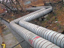 Long zigzag metal tubes, power industry details,. Few long zigzag metal power tubes with graffiti and abandoned place with refused garbage, power industry Stock Photo