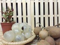 Longan στο καλάθι και φράκτης με flowerpot Στοκ Φωτογραφίες