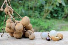 Longan φρέσκο Μια δέσμη Longan και της φλούδας σε ένα ξύλινο υπόβαθρο με το πράσινο φυσικό υπόβαθρο στον κήπο από τη βόρεια Ταϊλά Στοκ εικόνες με δικαίωμα ελεύθερης χρήσης