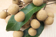 Longan and leaves sweet fruit on wood Royalty Free Stock Photography