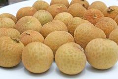 Longanfrukt på den vita plattan royaltyfri bild