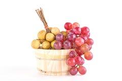 Longans en rode druiven in een rustieke houten emmer Stock Foto's