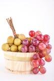 Longans en rode druiven in een rustieke houten emmer Royalty-vrije Stock Afbeeldingen