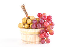 Longans and red grapes in a rustic wooden bucket Stock Photos