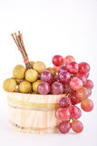 Longans and red grapes in a rustic wooden bucket Royalty Free Stock Images