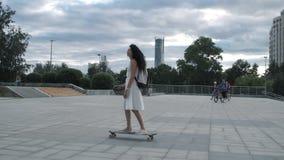 longboard骑马的女孩在街道 股票录像