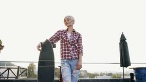 Longboard владением девушки красивого хипстера белокурое на крыше в современном здании в солнечной погоде Молодая женщина портрет видеоматериал