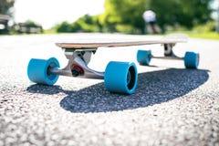 Longboard на дороге в солнечной погоде Люди вокруг скейтборда Тропа в парке место урбанское Стоковая Фотография