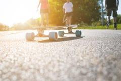 Longboard на дороге в солнечной погоде Люди вокруг скейтборда Тропа в парке место урбанское Стоковое Изображение