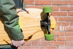 Longboard adolescente del control cerca de la pared de ladrillo Cierre para arriba Imagen de archivo