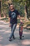 Longboard, das - ein longboarder aufwirft neben seinem longboard eisläuft Stockbild