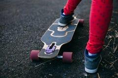 Longboard e primo piano delle scarpe di sport Fotografia Stock Libera da Diritti