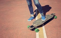 Longboard girl on the street at beautiful summer day. Toned in warm colors. Royalty Free Stock Photos
