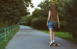 Longboard hermoso del montar a caballo de la chica joven Fotografía de archivo