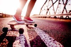 Longboard-Mädchen auf der Straße, langes Brett Stockbilder