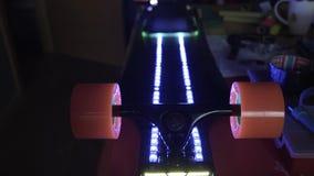 Longboard met LEIDENE lichte verlichting Het assembleren van skateboard met motor Koolstofbureau voor extreme sport Rit het schaa stock video