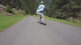 Longboard novo profissional da equitação do skater para baixo a estrada lateral do país vazio na paisagem bonita da floresta video estoque