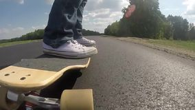 Longboardclose-up, voeten op een skateboard stock footage