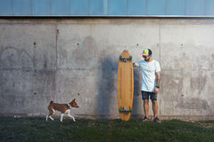 Longboarder with basenji dog next to gray concrete wall Royalty Free Stock Images