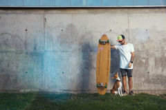 Longboarder with basenji dog next to gray concrete wall stock photo