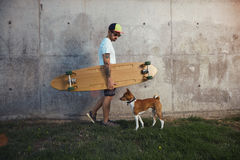 Longboarder with basenji dog next to gray concrete wall Royalty Free Stock Photo