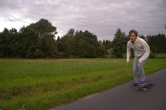 Longboarder going up the hill with speed, horizontal shot with copy space Stock Photos