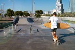 Longboarder i skridsko parkerar med hans hund arkivfoton