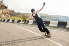 Longboarder on longboard in overalls helmet and gloves performs a stand-up slide at speed while on a mountain road Royalty Free Stock Image