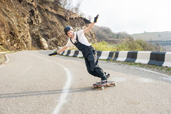 Longboarder on longboard in overalls helmet and gloves performs a stand-up slide at speed while on a mountain road Royalty Free Stock Photography
