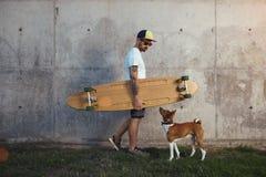 Longboarder med basenjihunden bredvid den gråa betongväggen royaltyfria bilder