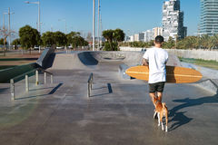 Longboarder in skate park with his dog Stock Photos