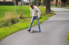Longboarder on the street getting back onto board Stock Photo