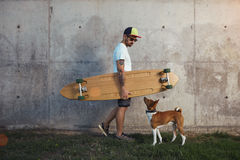 Longboarder z basenji psem obok szarej betonowej ściany obrazy royalty free
