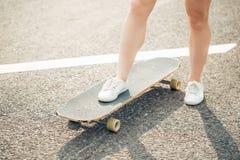 Longboarding y concepto de la gente - piernas femeninas que montan en longboard a lo largo del camino Imagen de archivo