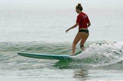 Longboard冲浪者女孩抓住波浪Wahine经典之作  免版税图库摄影