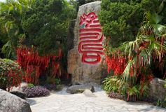 Longevity Valley, Sanya. Large stone with inscription in Chinese calligraphic characters relating to long life surrounded by bushes covered with red wishes in Stock Image