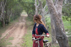 Longhair girl looking back. With bicycle in her hand Royalty Free Stock Photo