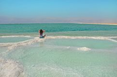 longhaired женщина брюнет сидя на соли намочите поверхность мертвого моря в Израиле с взглядом горы Джордана сливать природу стоковая фотография rf