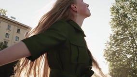 Longhaired милая девушка имбиря в зеленом платье закручивая на городскую площадь видеоматериал