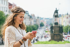 Longhaired bohemian young lady writing sms on mobile, Prague Royalty Free Stock Photos