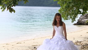 longhaired bride sits on sand and stands up against sea and island stock video