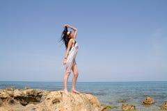 Longhaired brunetka w czarnym bikini cieszy się lato przy plażą Obraz Stock