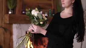 Longhaired female florist holding a half made bouquet and adding flowers and plants to composition. Designing, floral. Workshop, leisure. Blurred picture of stock video