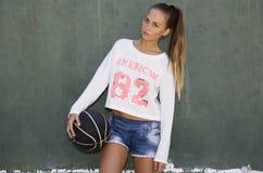 Longhaired flicka som rymmer en boll Fotografering för Bildbyråer