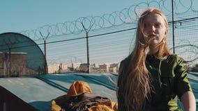 Longhaired gember mooi meisje in groene kledingszitting op dakwerk met weerhaakdraad stock footage