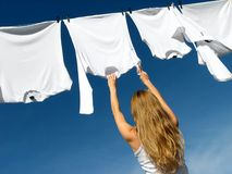 Longhaired girl, blue sky and white laundry. Longhaired young woman reaching white laundry which hangs to dry in a summer breeze on a clothes-line royalty free stock image